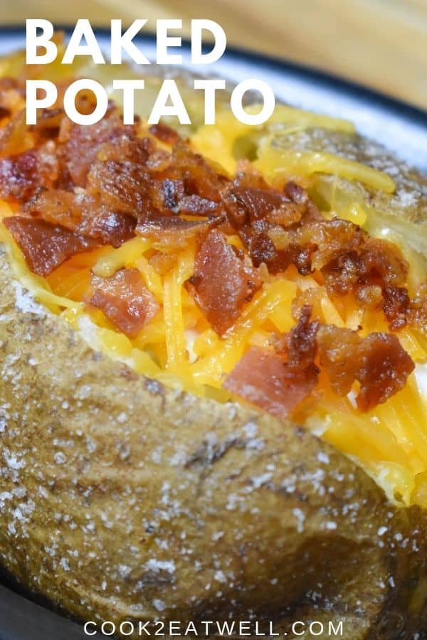 A close up of a baked potato with melted cheddar cheese and chopped bacon.