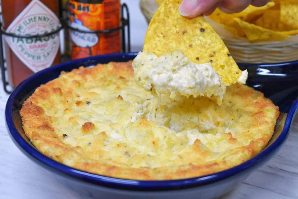 A tortilla chip scooping up some hot artichoke dip with hot sauce in the background.