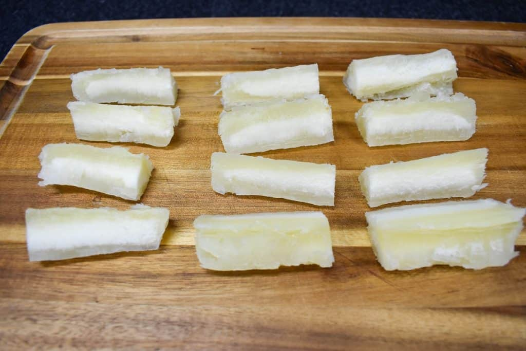Cook yuca cut into thick pieces displayed on a wood cutting board.