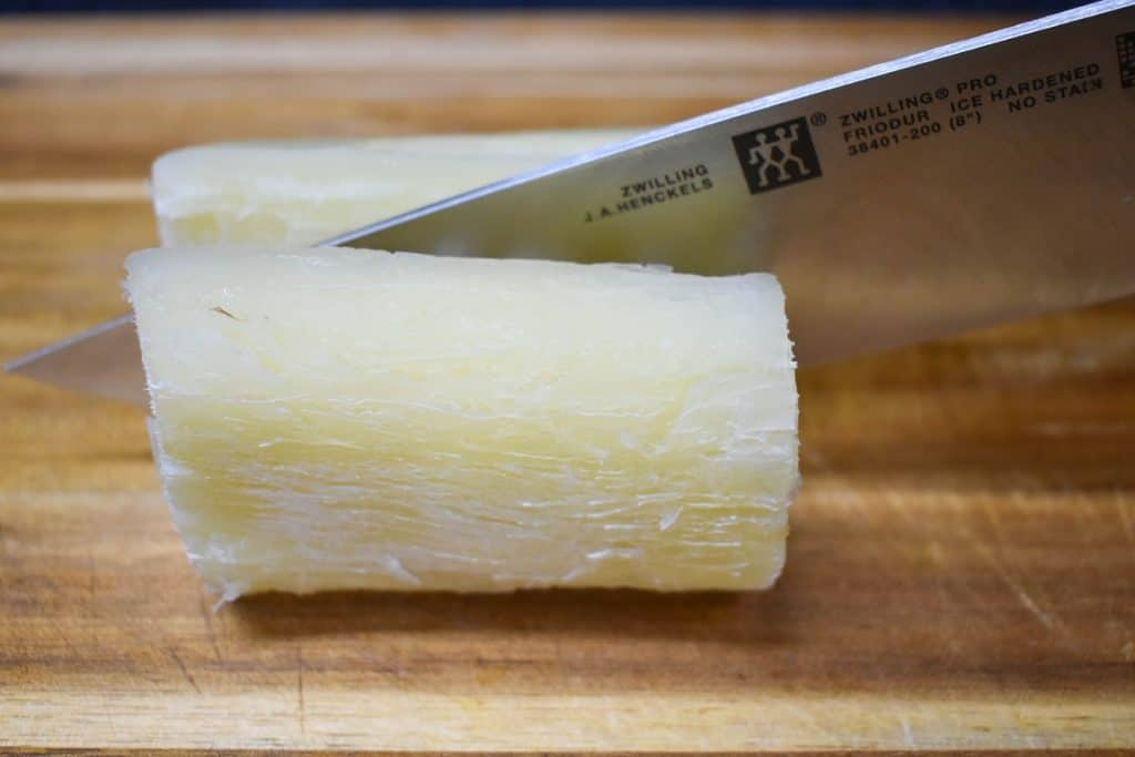 A piece of cooked yuca being cut in half by a large knife on a wood cutting board.
