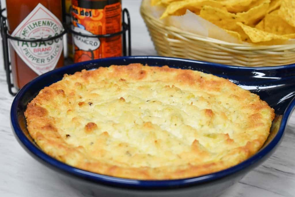 Hot artichoke dip in a blue baking dish with hot sauce and chips in the background.
