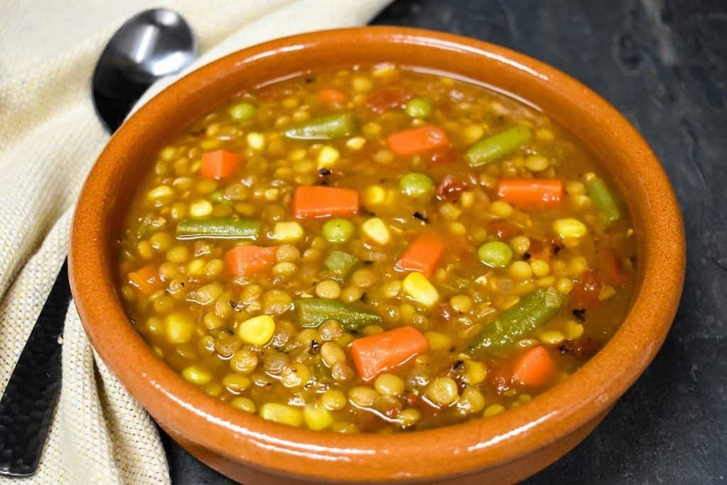 A close up picture of the lentil vegetable soup served in a red clay bowl.