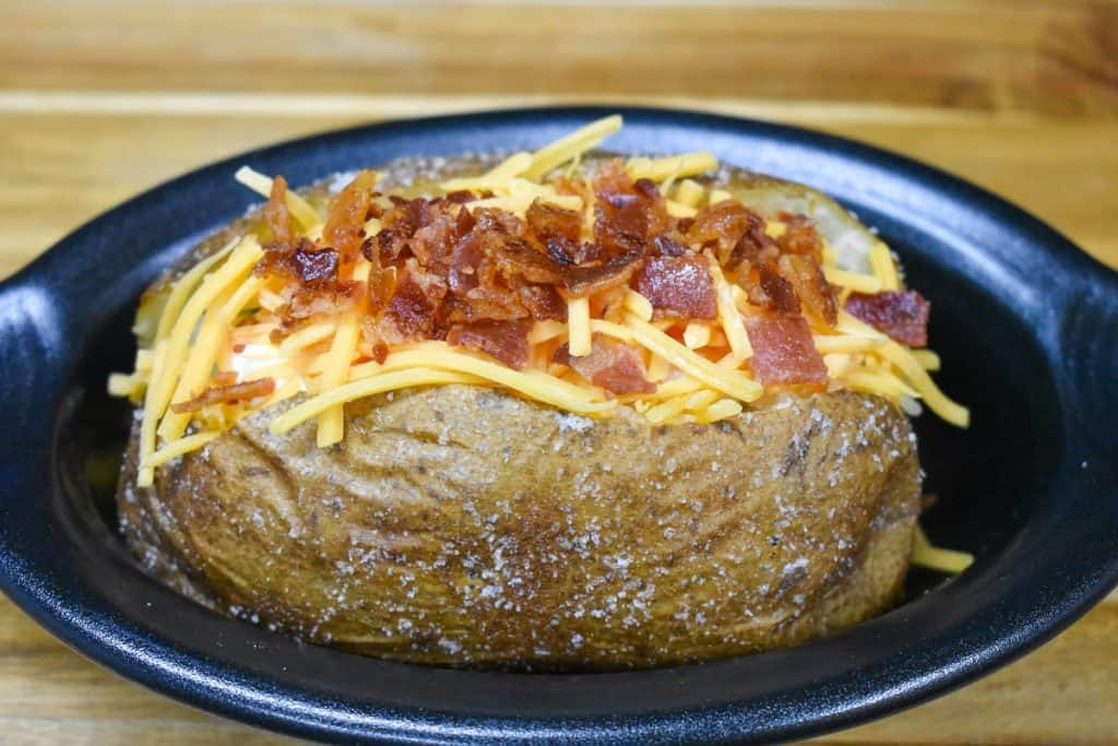 A baked potato with shredded cheese and chopped bacon on top, served in a small black crock.