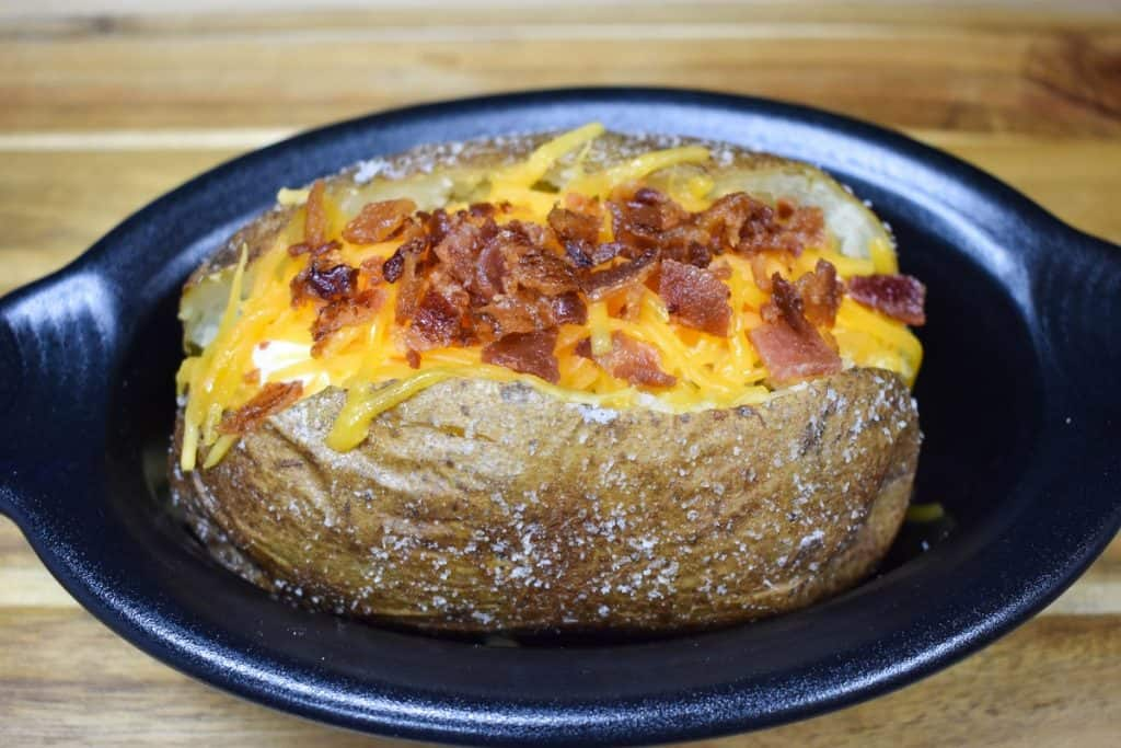 A baked potato with melted shredded cheese and chopped bacon on top, served in a small black crock.
