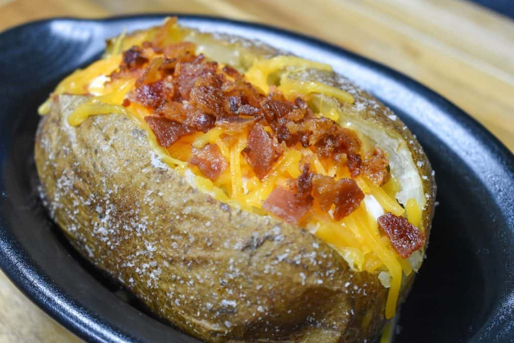 A close up image of a baked potato with melted shredded cheese and chopped bacon.