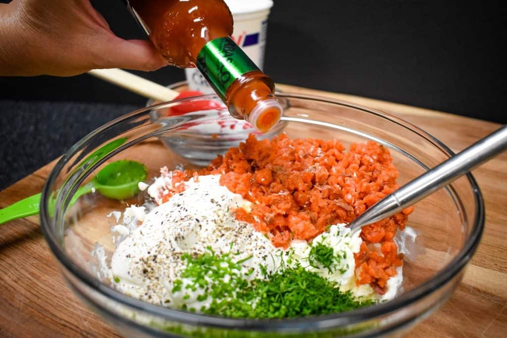 The ingredients for the salmon dip in a large, clear bowl with drops of hot sauce being added.
