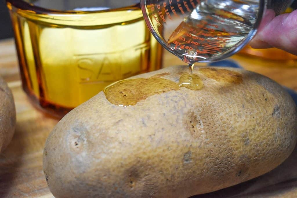 A small amount of oil being poured on a large russet potato, with an amber colored salt cellar in the background.
