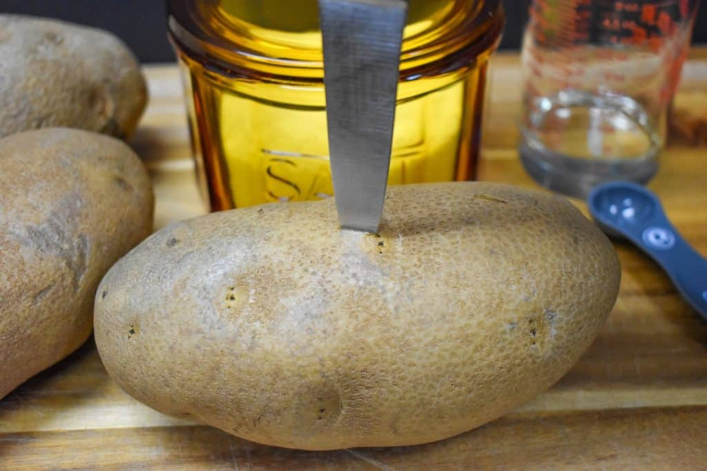 A large russet potato being pricked by a paring knife.
