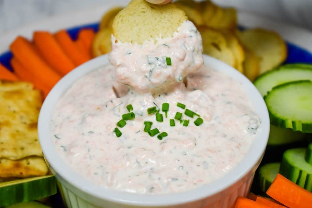 A close up picture of salmon dip being scooped by a bagel chip.