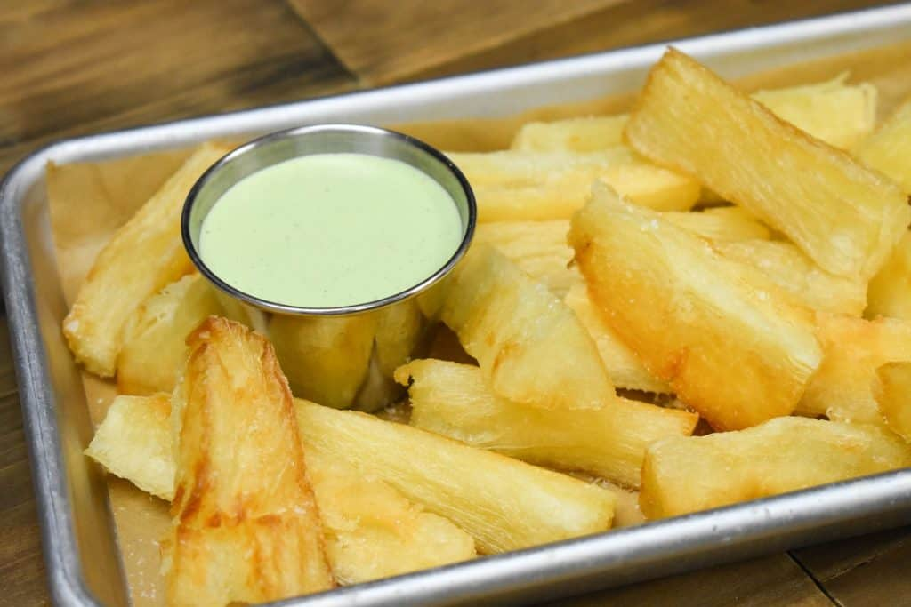Fried yuca served with a light green cilantro sauce, served in a small metal pan.