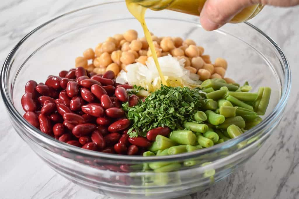 Dressing being added to red kidney beans, garbanzo beans, green beans, sliced onions and chopped parsley in a large, glass bowl.