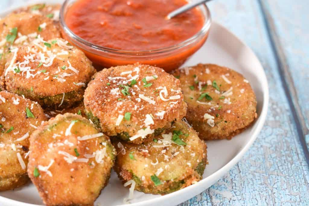 Breaded and fried zucchini rounds displayed on a white plate with a small bowl of red sauce in the background.