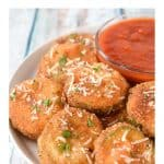 Fried zucchini rounds arranged on a white plate with a small bowl of marinara sauce.
