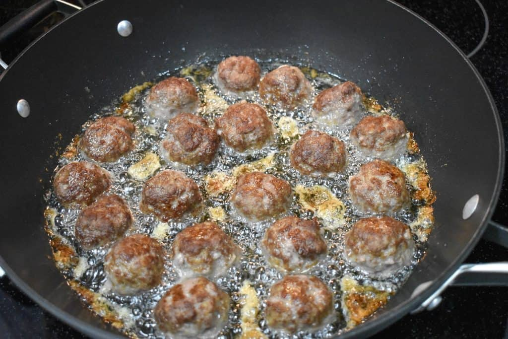 Browned small meatballs frying in oil in a large, black skillet.