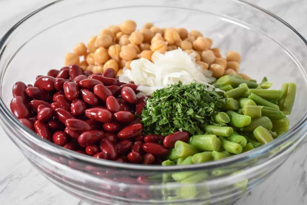 Red kidney beans, garbanzo beans, green beans, sliced onions and chopped parsley arranged in a large, glass bowl.