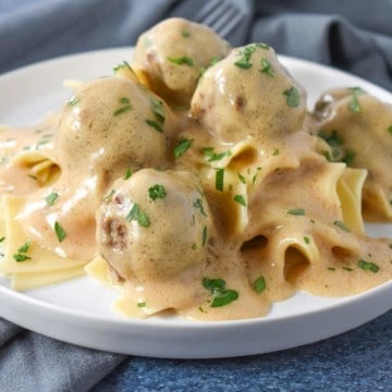 Small meatballs smothered in a light colored gravy served on a bed of egg noodles on a white plate.