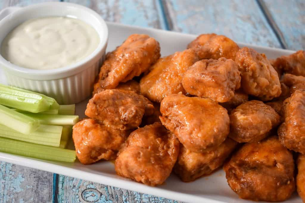 Buffalo chicken bites served on a white platter with a side of blue cheese dressing and celery sticks.