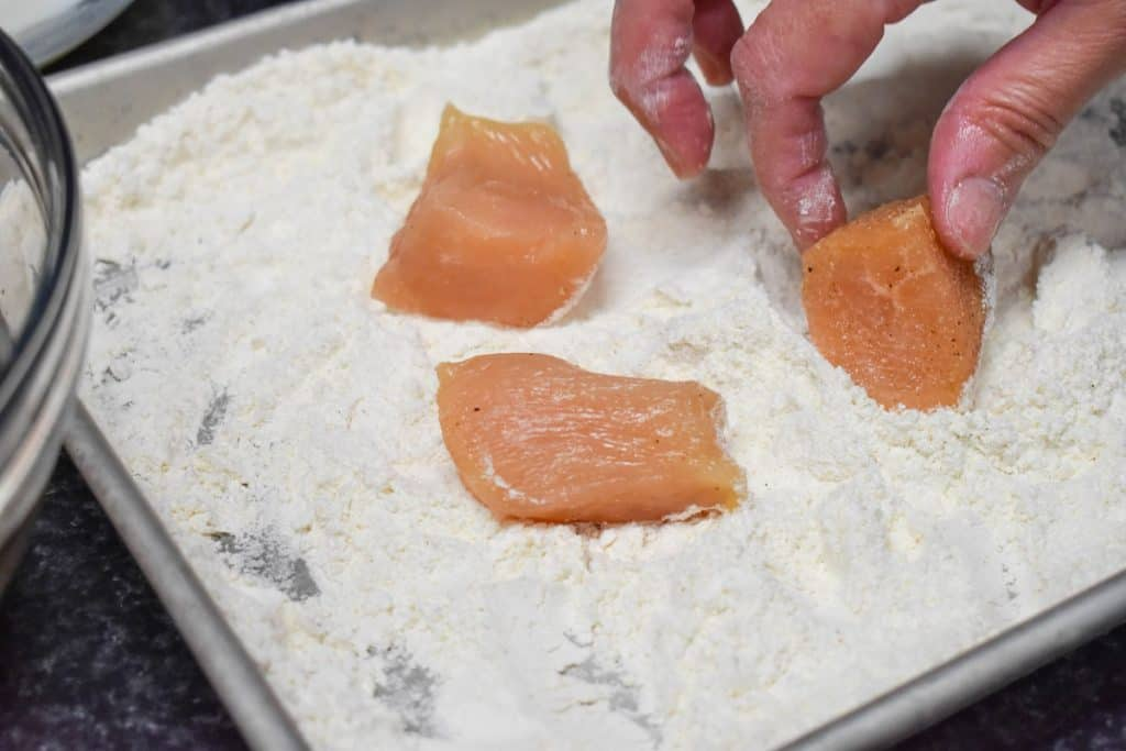 Three small pieces of raw chicken being coated in flour.