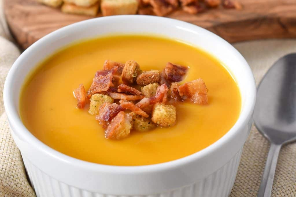 Creamy butternut squash soup served in a large, white ramekin and garnished with bacon bits and croutons.