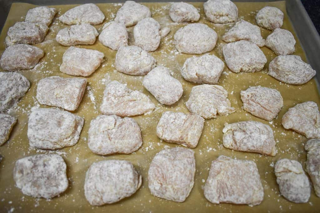 Small pieces of chicken breasts coated in flour and displayed on a large, parchment lined baking sheet.