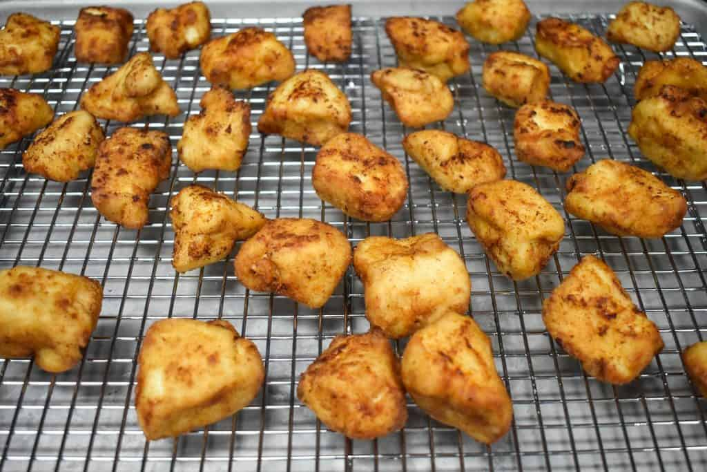 Fried chicken bites on a large cooling rack.