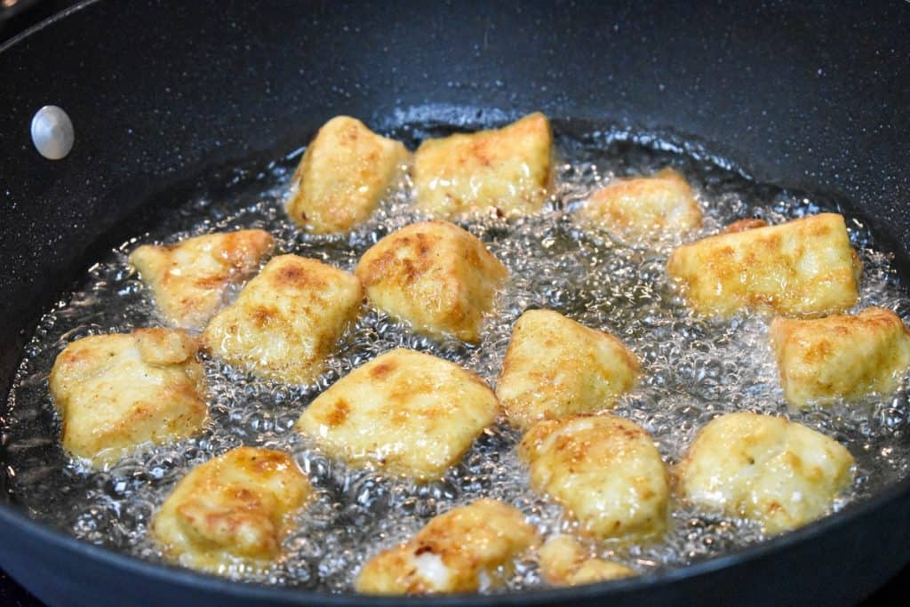 Flour coated chicken pieces frying in oil in a large, black skillet.