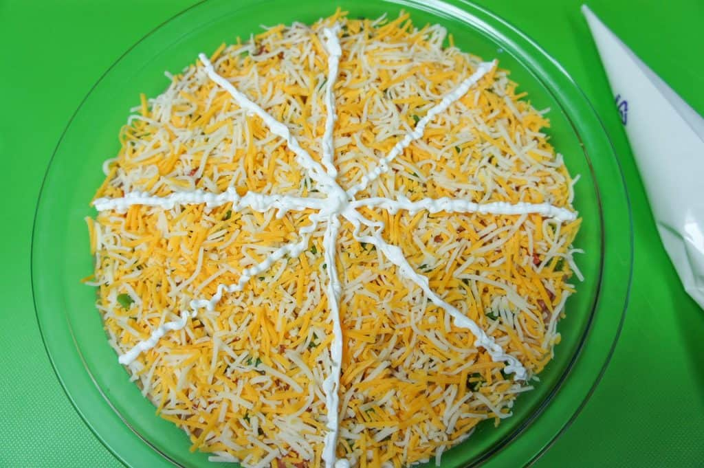 Sour cream lines on the cheese covered bean dip in a glass pie plate.
