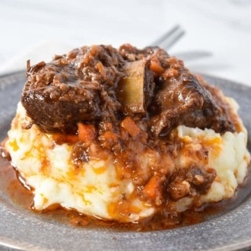 Short ribs and sauce served on a bed of mashed potatoes on a gray plate.