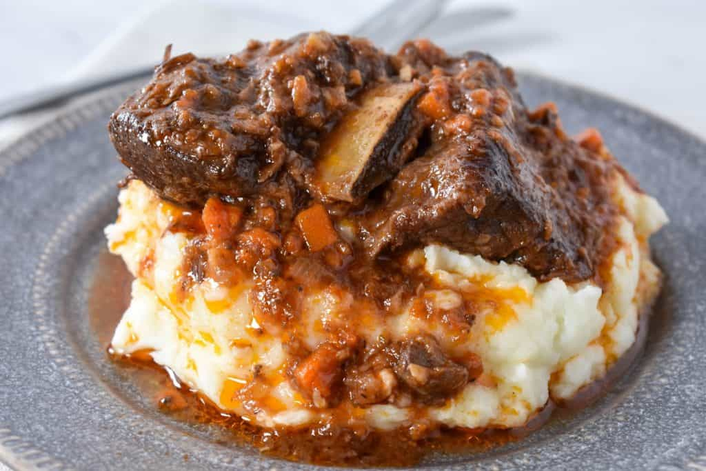 A close up picture of short ribs and sauce served on a bed of mashed potatoes on a gray plate.