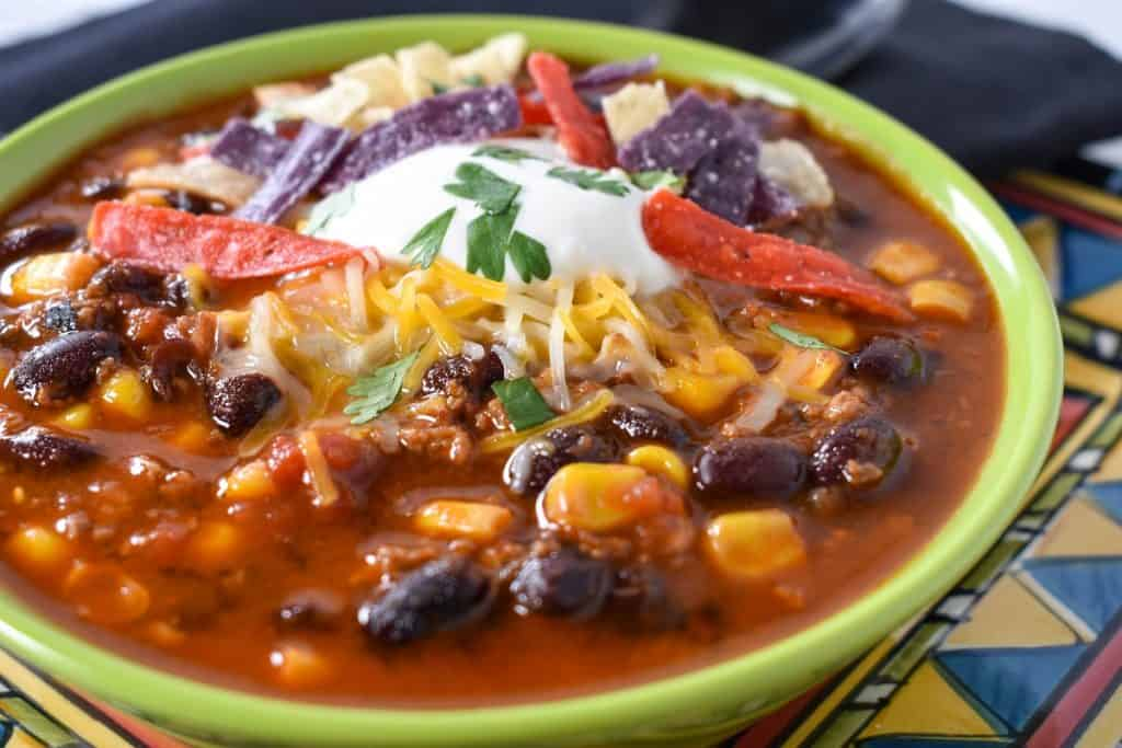 A close up image of taco soup garnished with sour cream, shredded cheese and tortilla strips.