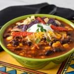 Turkey taco soup served in a green bowl and set on a colorful southwestern style plated with a black napkin and spoon in the background.