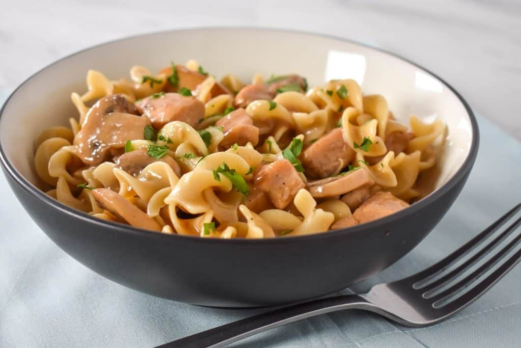 Egg noodles, cubed chicken and sliced mushrooms served in a white bowl on a light blue linen.