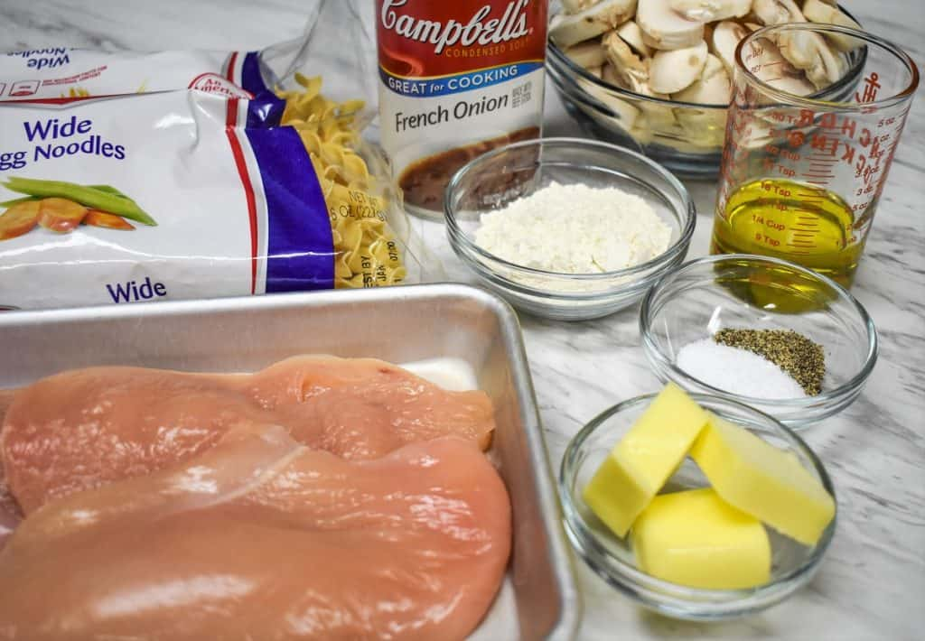 The ingredients for the chicken and noodles recipe displayed on a white table.
