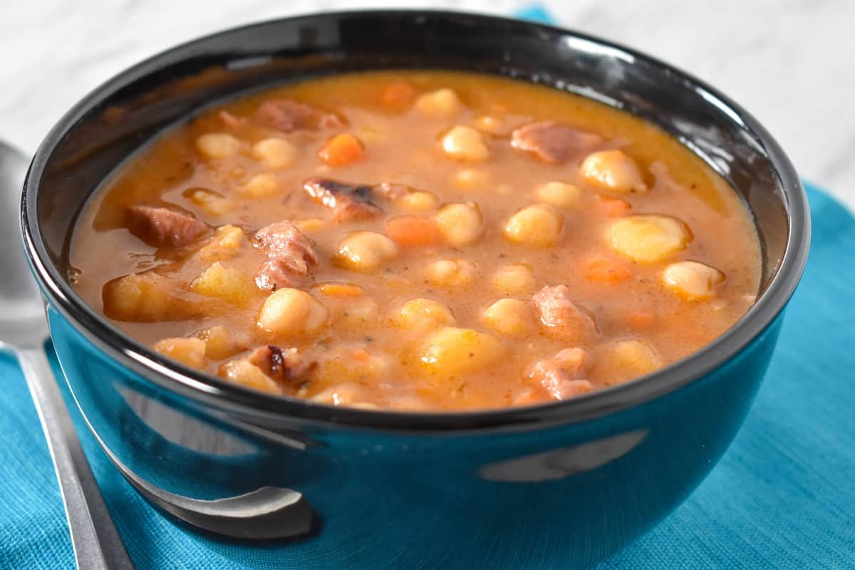 A close up image of chickpea soup served in a black bowl.