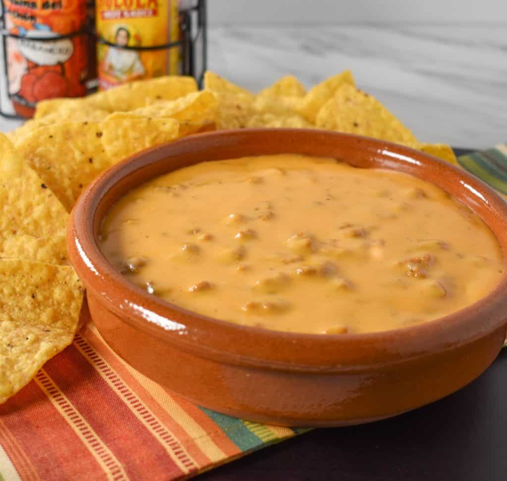 Chorizo Cheese Dip served in a terracotta crock with tortilla chips and hot sauce in the background.