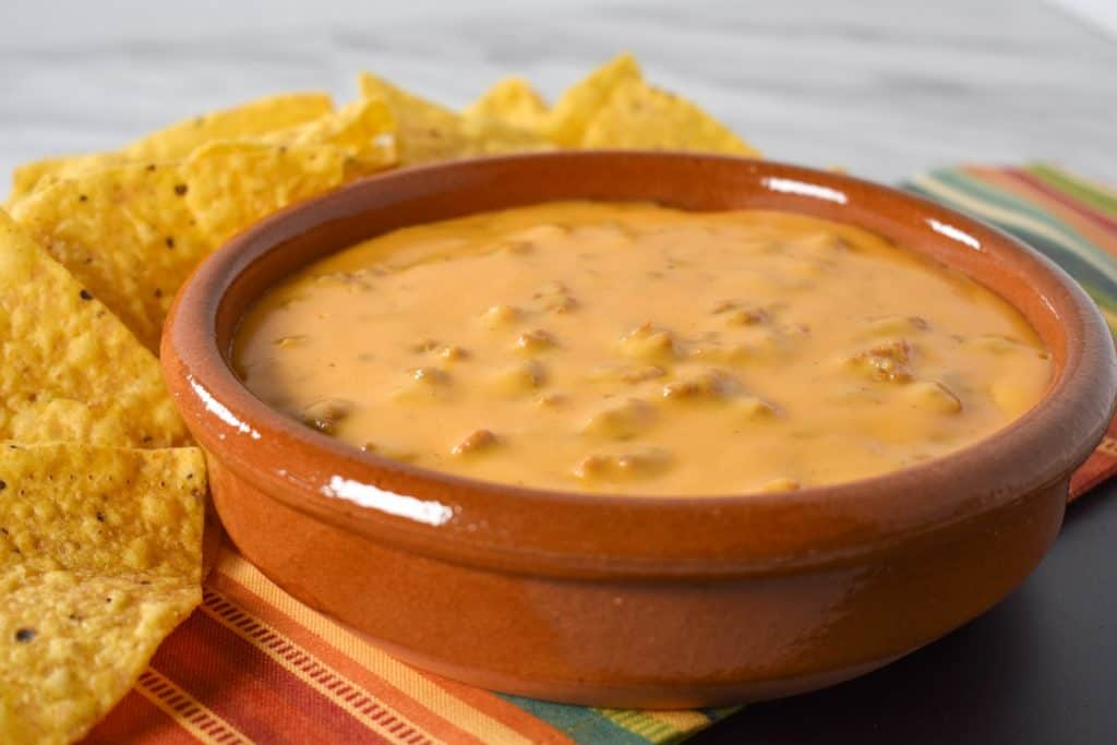 Chorizo cheese dip served in a terracotta crock with tortilla chips in the background.