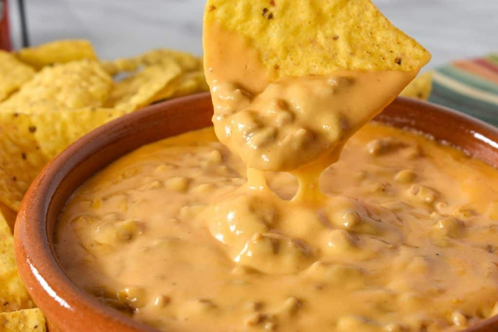 A tortilla chip dipped in the chorizo cheese dip.