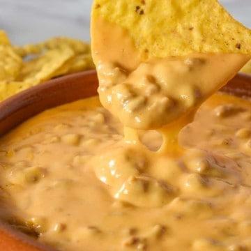 A tortilla chip dipped in the chorizo cheese dip.
