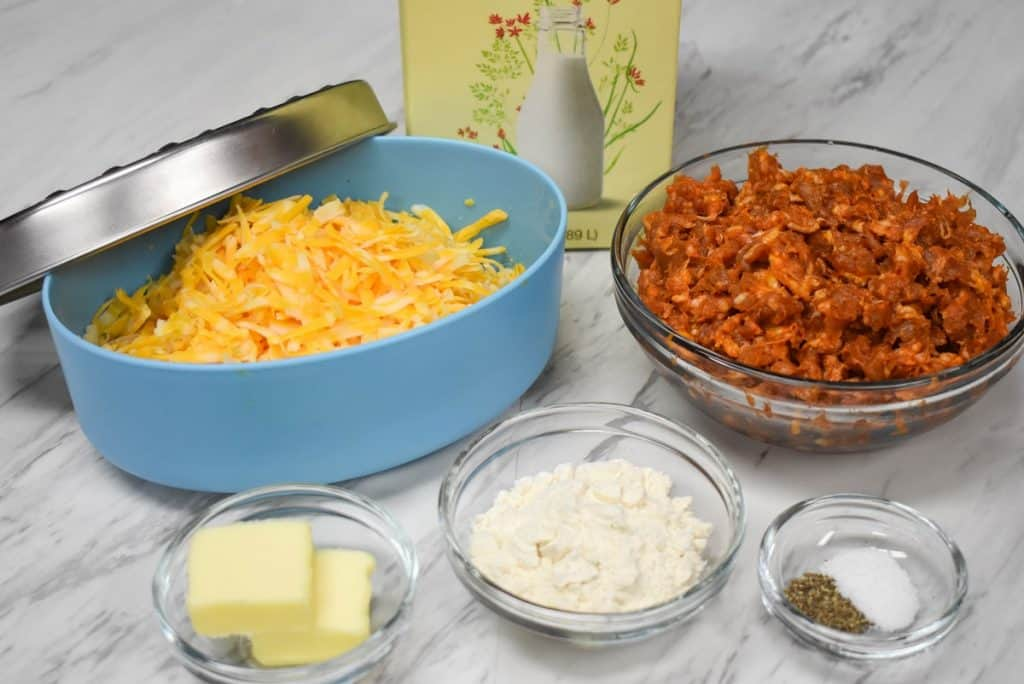The ingredients for the chroizo cheese dip arranged on a white table.
