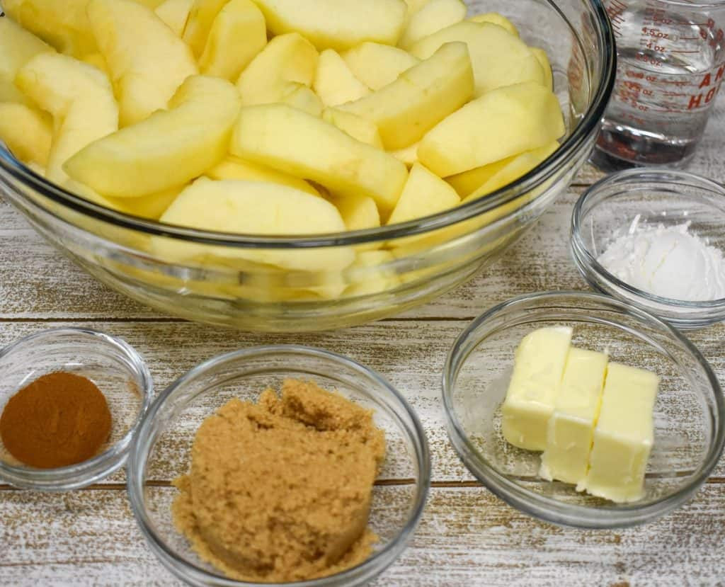 Sliced, peeled apples in a large bowl with cinnamon, brown sugar, butter and corn starch in smaller bowls.