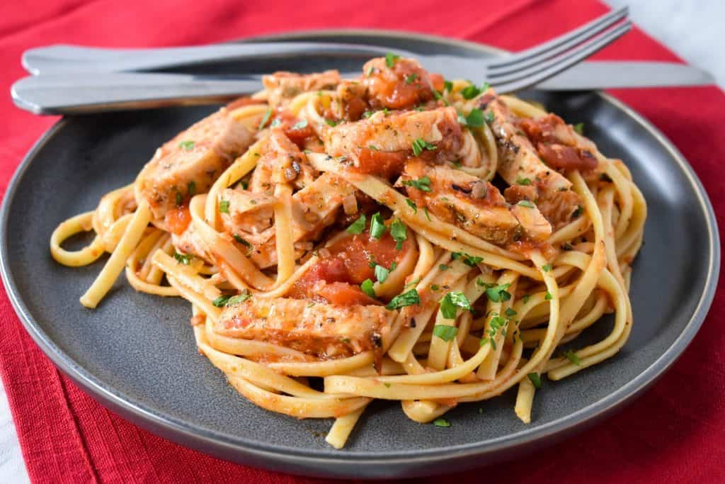 Linguine noodles tossed with tomatoes and sliced chicken breast served on a gray plate on a red cloth napkin.
