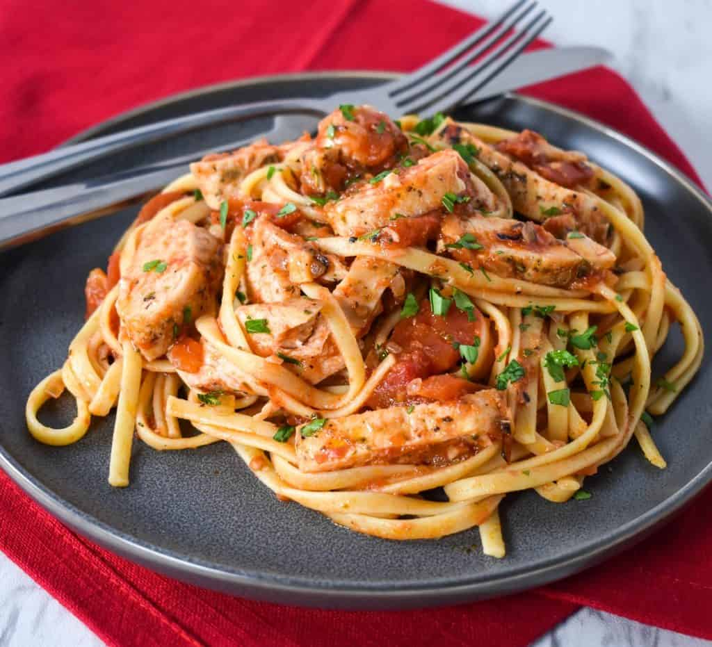 Linguine noodles tossed with tomato sauce, sliced chicken breasts and garnished with parsley, served on a gray plate.