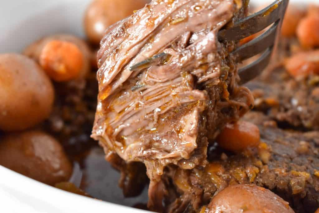 A large piece of pot roast being lifted by a serving fork.