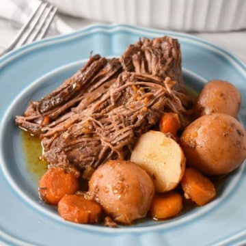 Pot roast served with carrots and small red potatoes on a light blue plate.