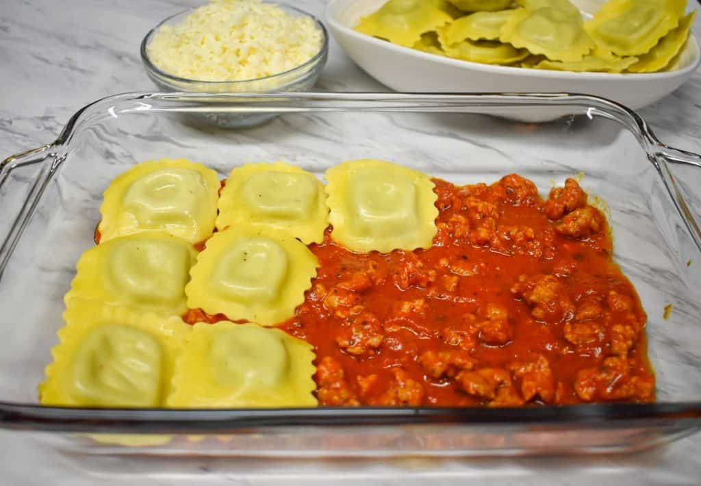 Ravioli being layered on sausage pasta sauce in a glass casserole dish.