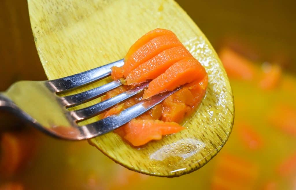 A carrot piece being pressed with a fork to demonstrate it is tender.