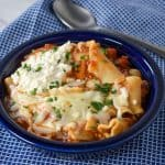 Lasagna Soup served in a blue bowl on a blue and white checkered linen.