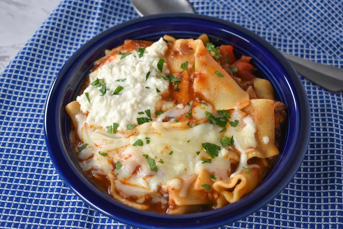 Lasagna soup served in a blue bowl on a blue checkered linen.