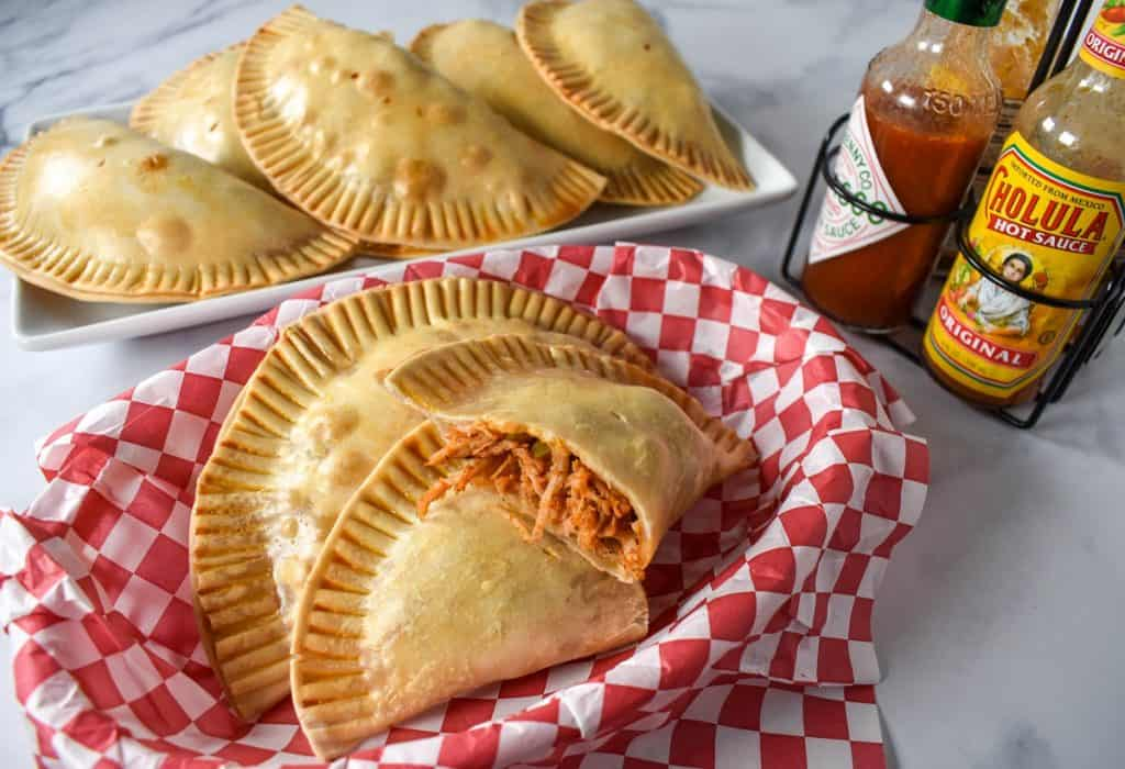 Chicken empanadas in a basket lined with a red and white checkered paper with hot sauce and a platter of empanadas in the background.