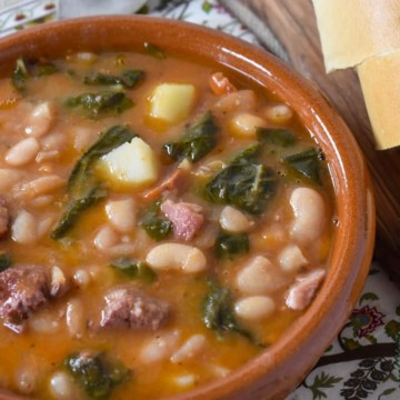 Cuban white bean soup served in a terracotta bowl with sliced bread on the side.